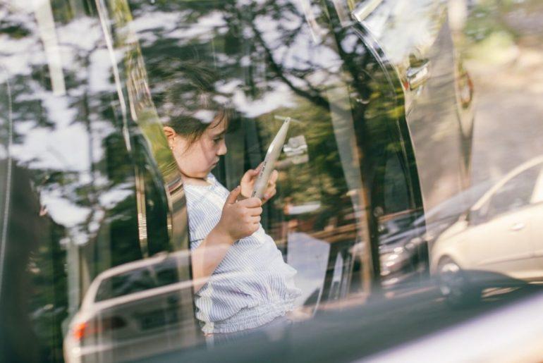 Girl using device in car.