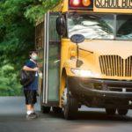 Boy in mask getting on school bus.