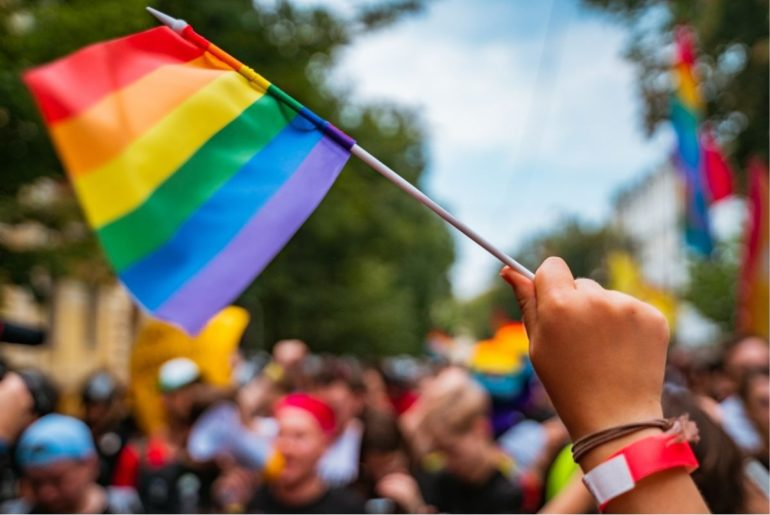 Close up of a rainbow flag being waved.