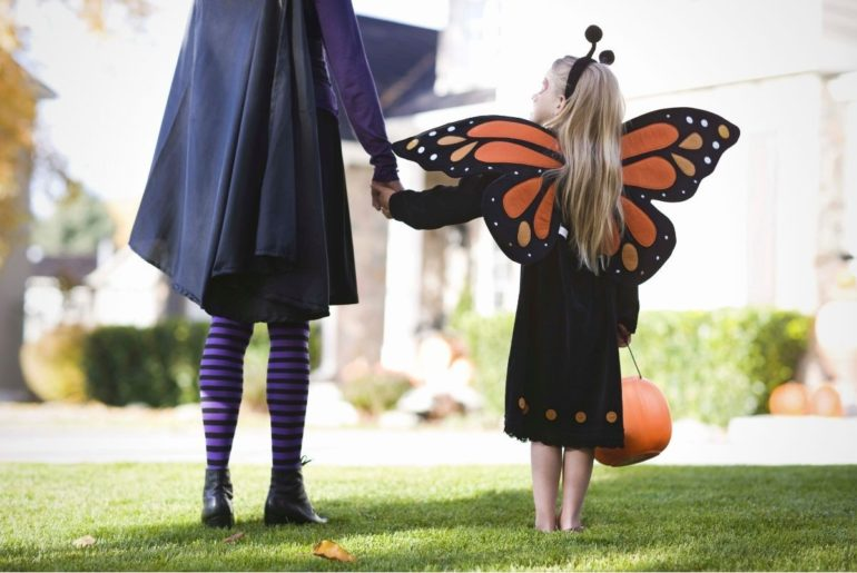 Girl in butterfly costume holding mom's hand.