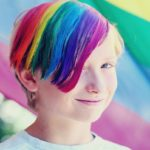 Child with rainbow colored hair smiling.