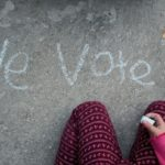"Child writing ""We Vote"" in chalk."