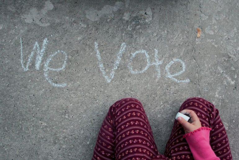 """Child writing """"We Vote"""" in chalk."""