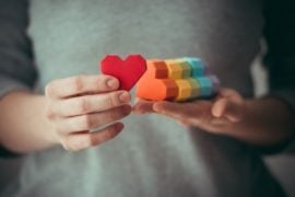 A person holding a set of multi colored wooden hearts.