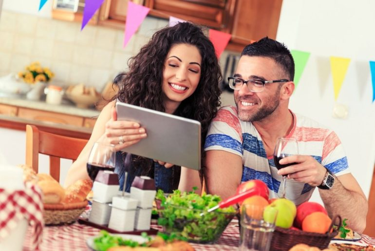 Couple enjoying dinner while looking at a tablet.