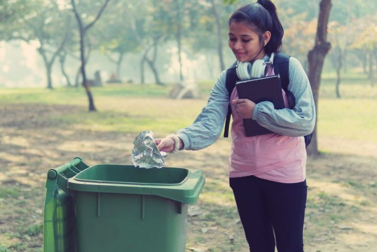 Girl in a park throwing paper in the trash.