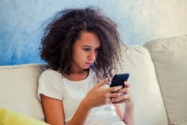 Teen girl with curly hair using smartphone.