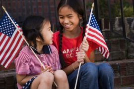 Smiling girls holding American flags.