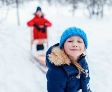 Kids playing happily in the snow.