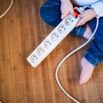 Young child playing with electrical surge protector outlet.