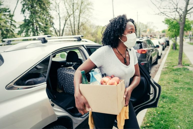 Woman carrying a box of food for delivery.