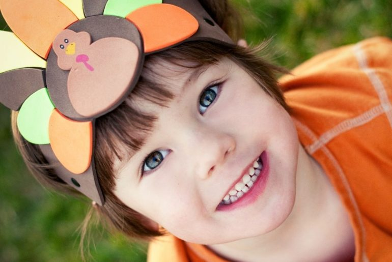 Child wearing turkey headband.