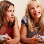 Two girls playing a video game, with one scowling at the other's grin.