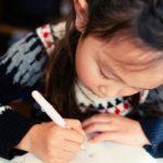 Little girl writing letter.