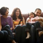 Family laughing on couch.