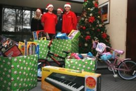 Toys for tots employees surrounded by wrapped gifts.