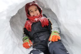 Boy smiling inside of a snow cave.