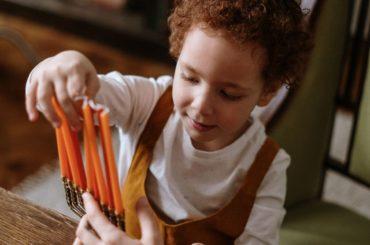 Child looking at Hanukkah menorah.