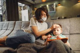 Mother wearing mask taking child's temperature.