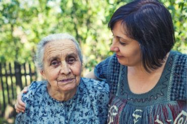Middle aged woman with aging mother in garden.