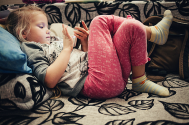 Young girl reclining with smartphone.
