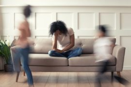 Image of mom on couch holding her head in her hand while kids run around.