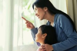 Mother and daughter pointing and looking out window.