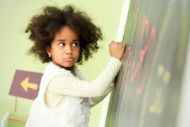 Young girl at chalkboard.
