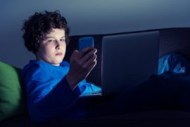 Teen boy on couch with laptop and smarthphone.
