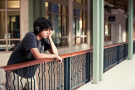 Sad boy leaning on balcony.