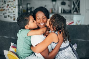 Mother hugging two children.