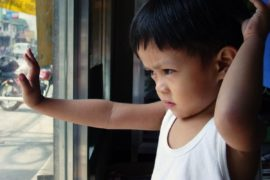 Young boy looking through window.