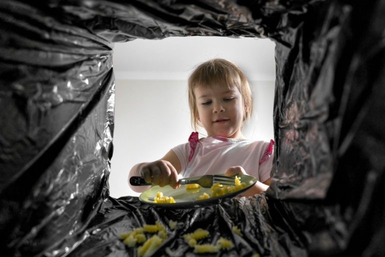 Young girl scraping food into trash.