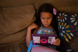 Tween girl on couch looking at tablet.