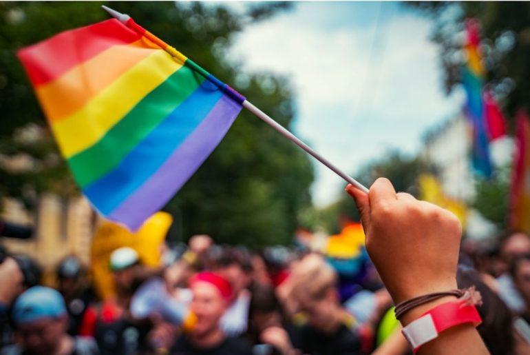 Hand holding LGBTQ flag at rally.