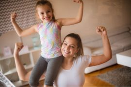 Mother and daughter showing their muscles.