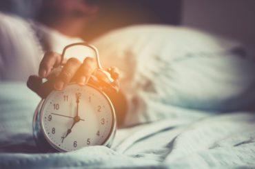 Hand on an alarm clock.