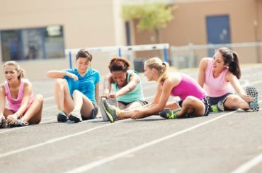 Teens stretching before running on a track.