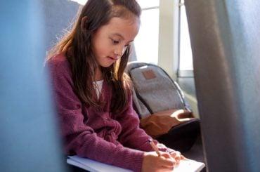 Girl on bus doing schoolwork.