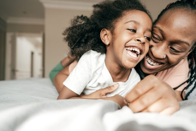 Parent and child laughing together on bed.
