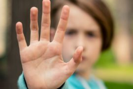 Child holding a hand up to signal stop.