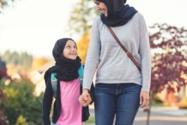 Mother and daughter walking while wearing head scarves.