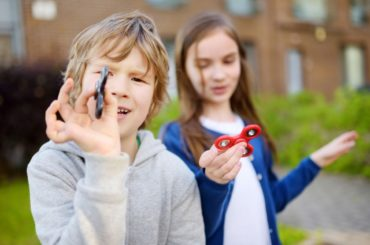 Two children playing with fidget spinners.