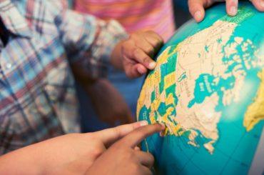 Kids pointing to globe.