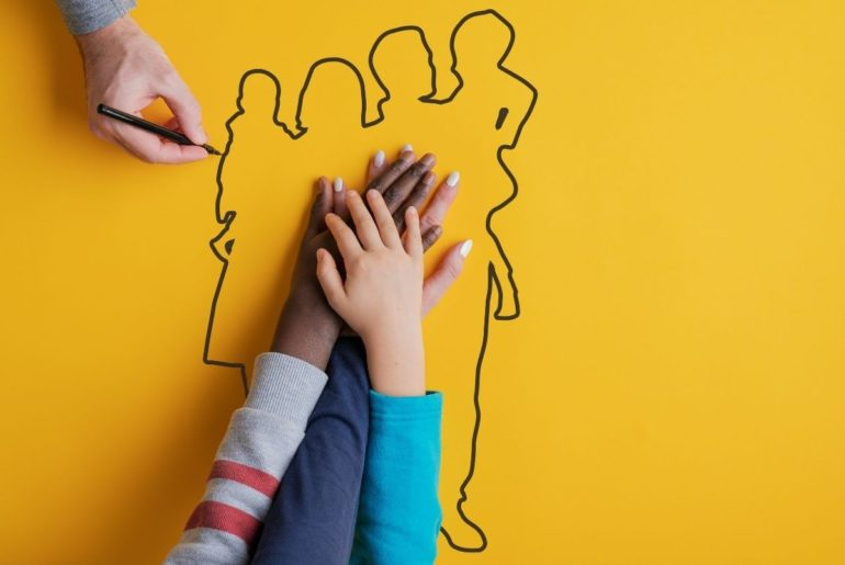 Foster family with hands overlapping on outline of a family drawing.