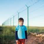 Young boy alone near tall border fence.