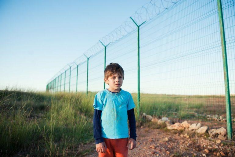 Young boy alone near tall border fence.