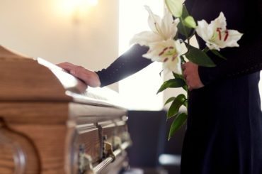 Woman with hand on casket.