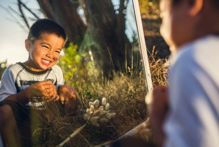 Boy looking in a mirror outdoors.