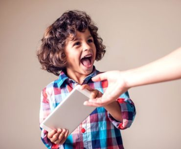 Adult taking tablet device from child.